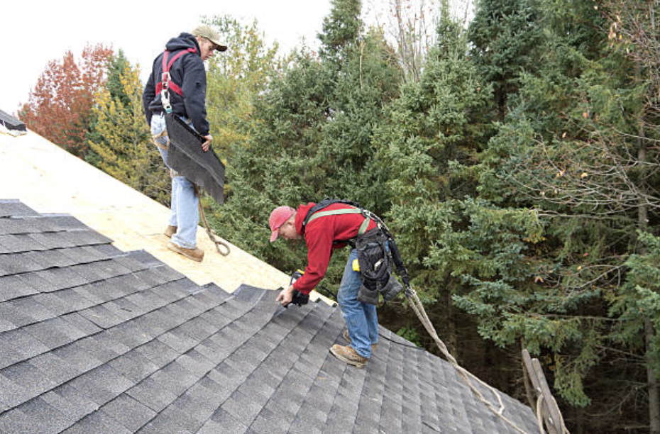 two roofing contractors, one in a red longsleeve sweatshirt repairing a roof in  Ontario CA